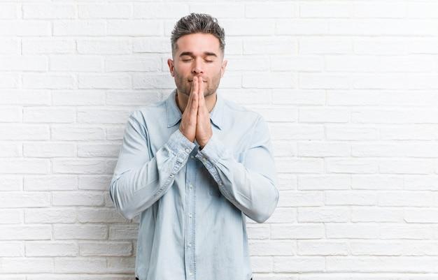 De jonge knappe mens tegen een bakstenen muurholding dient bidt dichtbij mond in, voelt zeker.