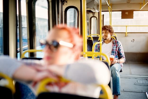 De jonge knappe mens zit op een buszetel terwijl hij koffie houdt en door het raam kijkt terwijl hij op aankomst op zijn bestemming wacht.