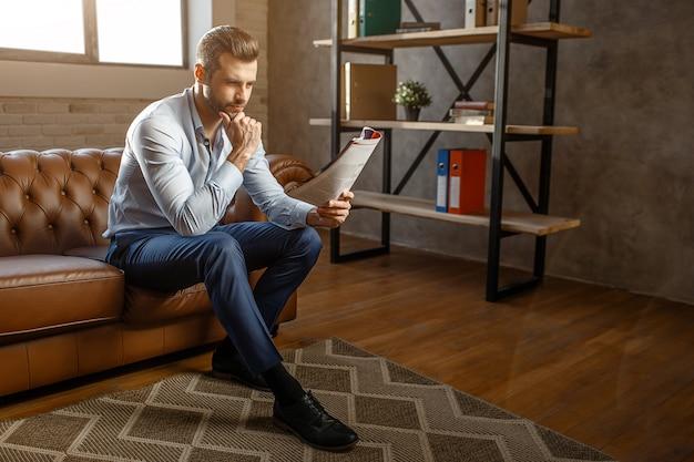 De jonge knappe nadenkende zakenman zit op bank en las dagboek in zijn eigen bureau. hij poseert. zelfverzekerd en sexy. daglicht.
