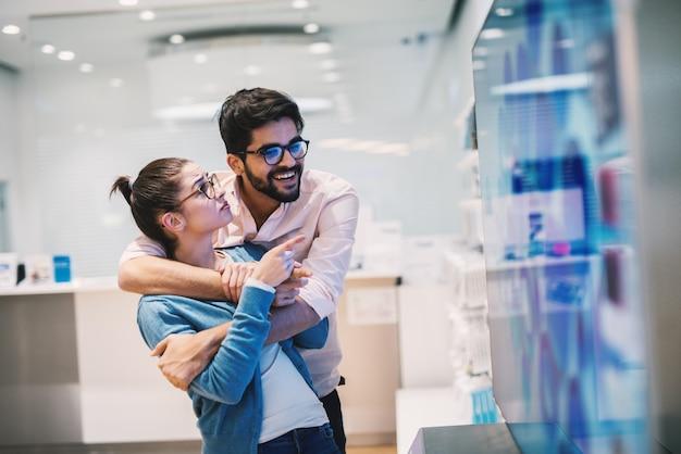 De jonge knappe vrolijke mens houdt zijn vriendin geknuffeld aangezien zij telefoons in een heldere winkel doorbladert.