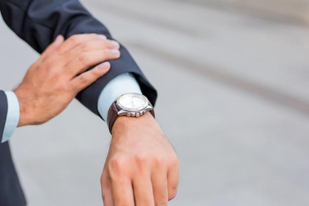 De jonge knappe zakenman die van azië zijn horloge bekijkt