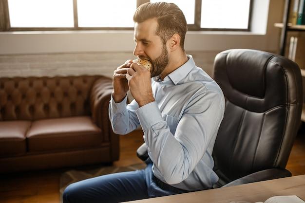 De jonge knappe zakenman eet hamburger in zijn eigen kantoor. hij zit aan tafel en bijt maaltijd. ongezond heerlijk. breken. daglicht.