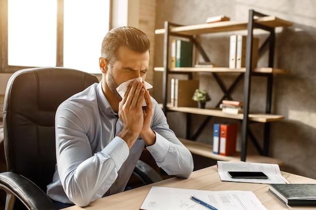 De jonge knappe zakenman zit aan tafel en niest in zijn eigen kantoor. hij bedekt de neus met wit servet. zieke man lijdt.