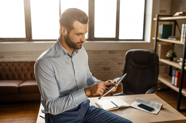 De jonge knappe zakenman zit op lijst en gebruikt tablet in zijn eigen bureau. hij ziet er geconcentreerd uit. telefoon en laptops op tafel. daglicht vanuit raam.