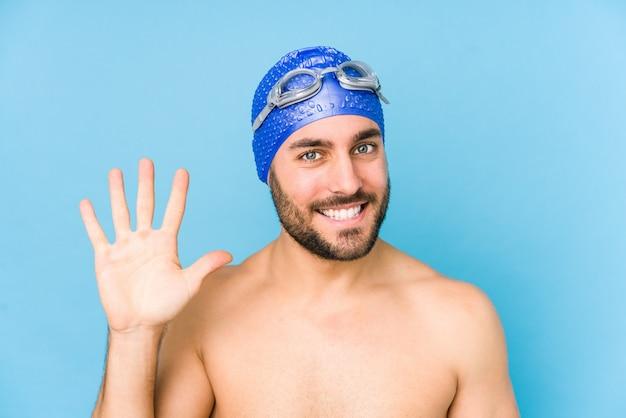 De jonge knappe zwemmersmens isoleerde het glimlachen vrolijk tonend nummer vijf met vingers.