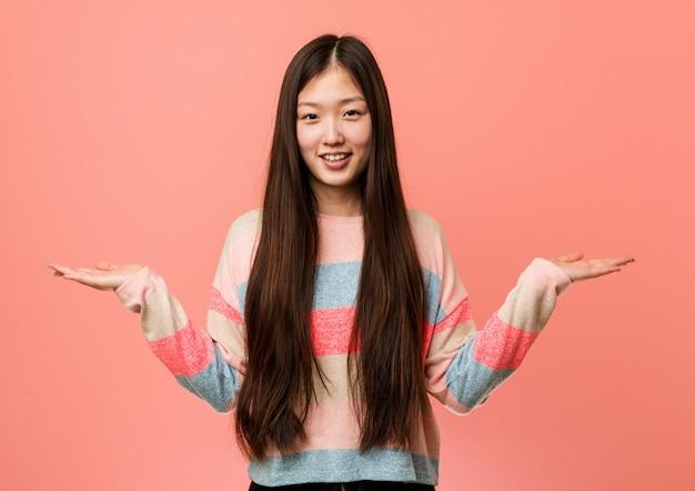 De jonge koele chinese vrouw maakt schaal met wapens, voelt gelukkig en zeker.