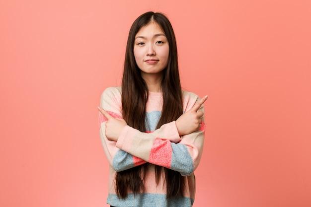 De jonge koele chinese vrouw wijst zijwaarts, probeert te kiezen tussen twee opties.