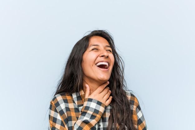 De jonge koele indische vrouw lacht hardop hand houdend op borst.