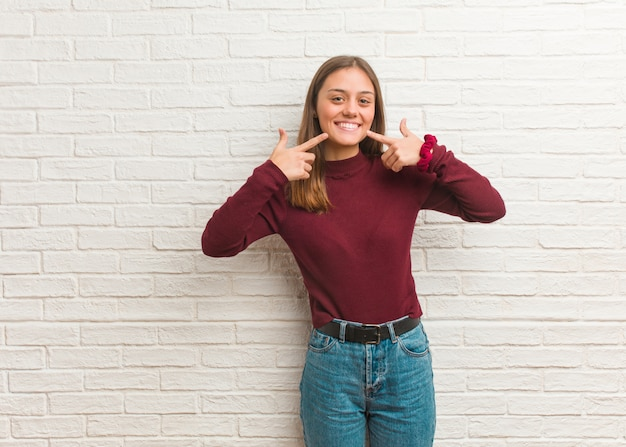 De jonge koele vrouw over een bakstenen muur glimlacht, wijzend mond