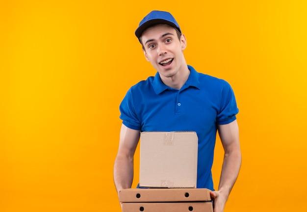 De jonge koerier die blauw uniform en blauw glb draagt, houdt gelukkig dozen