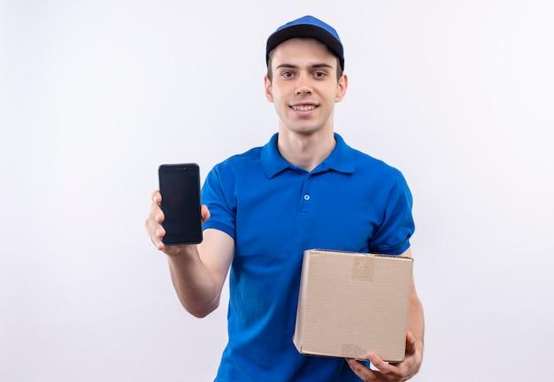 De jonge koerier die een blauw uniform en een blauwe pet draagt, houdt gelukkig een telefoon en een tas vast