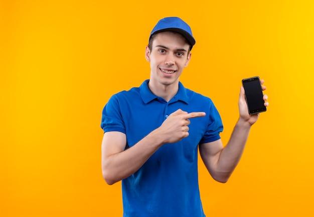 De jonge koerier die een blauw uniform en een blauwe pet draagt, wijst blij dat hij met wijsvinger belt