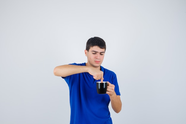 De jonge kop van de jongensholding dichtbij kin, dient het in blauw t-shirt in en kijkt nieuwsgierig, vooraanzicht.