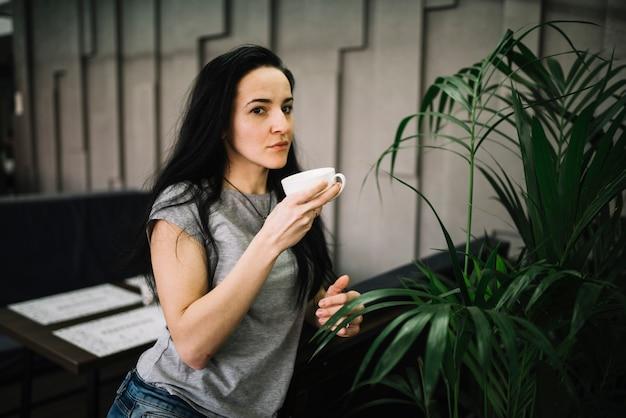 De jonge kop van de vrouwenholding van drank dichtbij lijst en banken