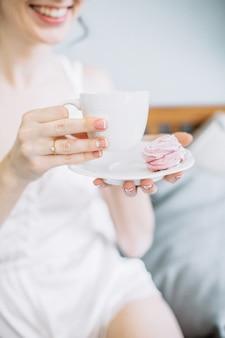De jonge kop van de vrouwenholding van koffie en koekje.