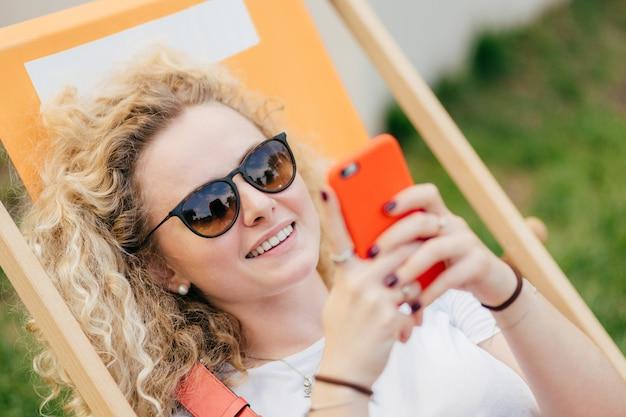 De jonge krullende blondevrouw ligt in hangmat, geniet van de zomerdag, bloggs en chats via slimme telefoon
