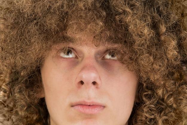 De jonge krullende mens bekijkt zijn haar met zijn ogen omhoog. zeer weelderige mannelijke kerel haar