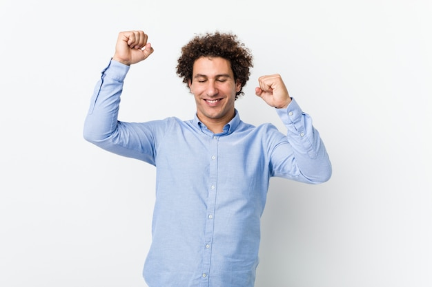 De jonge krullende rijpe mens die een elegant overhemd draagt dat een speciale dag viert, springt en heft wapens met energie op.