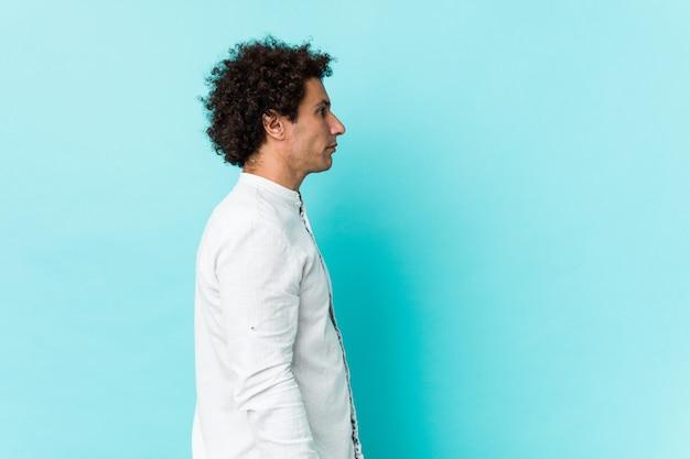 De jonge krullende rijpe mens die een elegant overhemd draagt dat links, zijdelings staart staart.