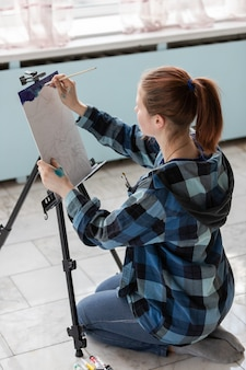 De jonge kunstenaar van de tienervrouw zit op de vloer van marmeren tegels. vrouw tijdens het schilderen met olieverven.