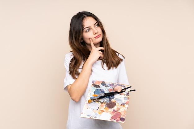 De jonge kunstenaarsmens die een palet op beige muur houden die twijfels hebben en verwart gezichtsuitdrukking