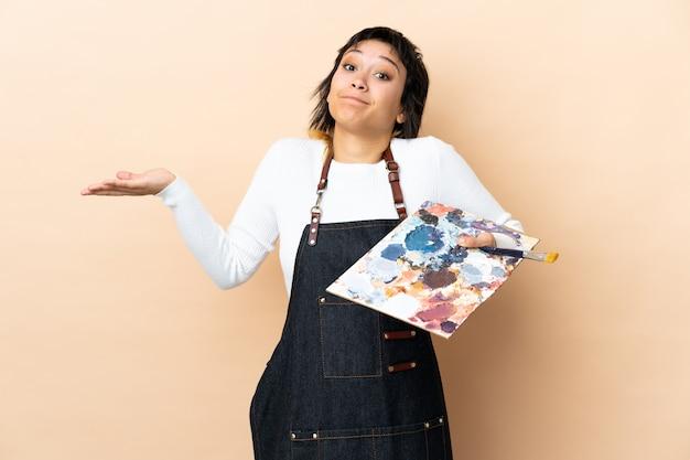 De jonge kunstenaarsmens die een palet over muur houdt die twijfels heeft met verwart gezichtsuitdrukking