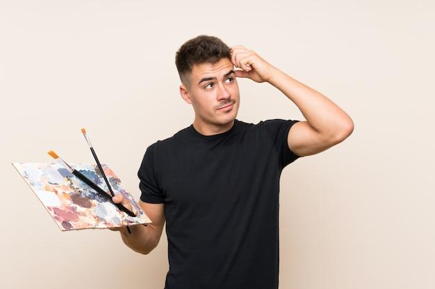 De jonge kunstenaarsmens over geïsoleerde muur die twijfels hebben en verwart gezichtsuitdrukking