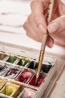 De jonge kunstenaarstekening bloeit patroon met waterverfverf en borstel op het werk