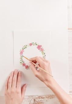 De jonge kunstenaarstekening bloeit patroon met waterverfverf en borstel op papier op het werk