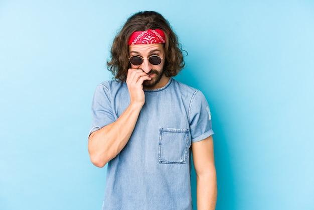 De jonge lange haarmens die een festival hipster draagt kijkt geïsoleerde bijtende vingernagels, zenuwachtig en zeer bezorgd.