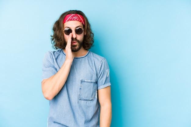 De jonge lange haarmens die een festival hipster dragen kijkt geïsoleerd zegt een geheim heet remmend nieuws en kijkt opzij