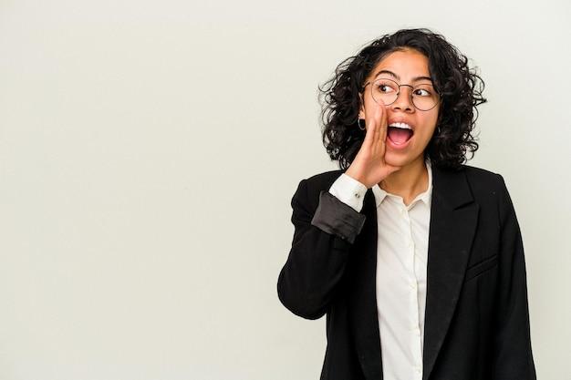 De jonge latijnse bedrijfsvrouw die op witte achtergrond wordt geïsoleerd, zegt een geheim heet remmend nieuws en kijkt opzij