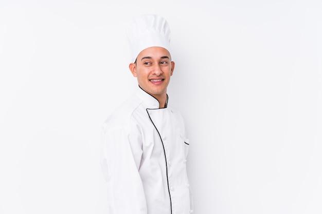 De jonge latijnse geïsoleerde chef-kokmens kijkt opzij glimlachend, vrolijk en aangenaam.
