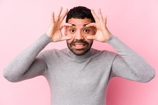 De jonge latijnse mens tegen een roze muur isoleerde het houden van ogen geopend om een succeskans te vinden.