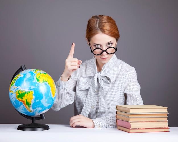 De jonge leraar in glazen met boeken en globe.