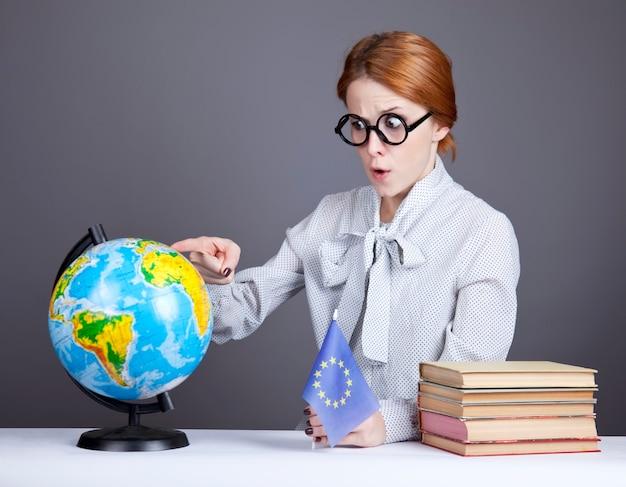 De jonge leraar in glazen met boeken