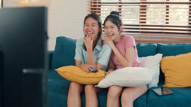 De jonge lesbische lgbtq vrouwen van azië koppelen thuis het letten op tv