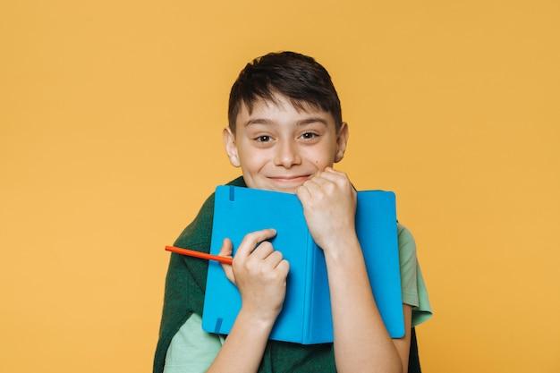De jonge leuke jongen, draagt lichtgroen overhemd en groene sweater, houdt blauw oefenboek en rood potlood en glimlacht gelukkig. modellen over gele muur. positief mensenconcept. vakantie begon