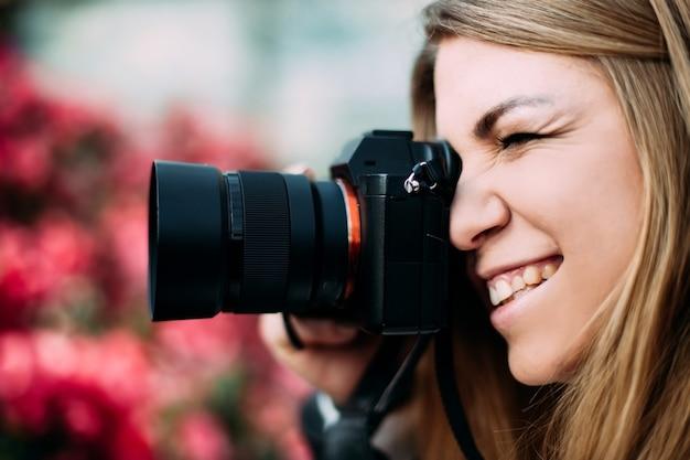 De jonge leuke meisjesfotograaf houdt een camera dichtbij het gezicht dat mensen fotografeert