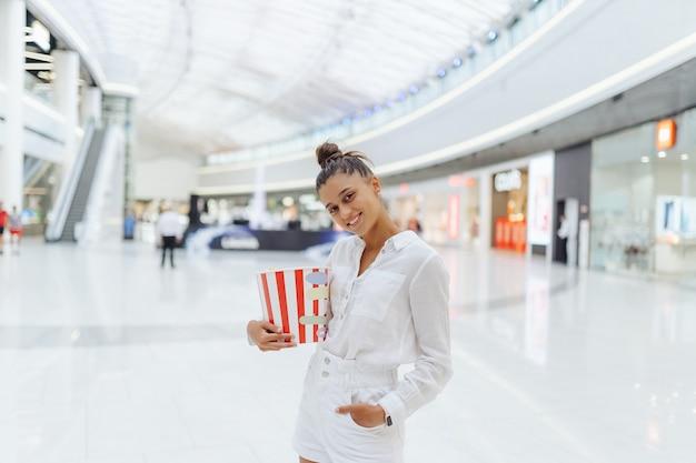 De jonge leuke popcorn van de vrouwenholding op de wandelgalerijachtergrond