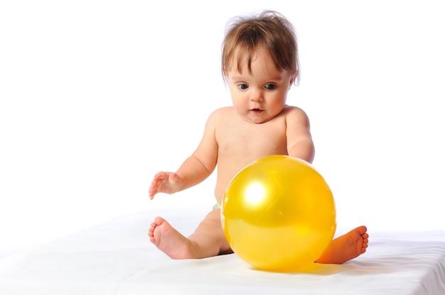 De jonge leuke voetballer van het babymeisje speelt met geel balportret