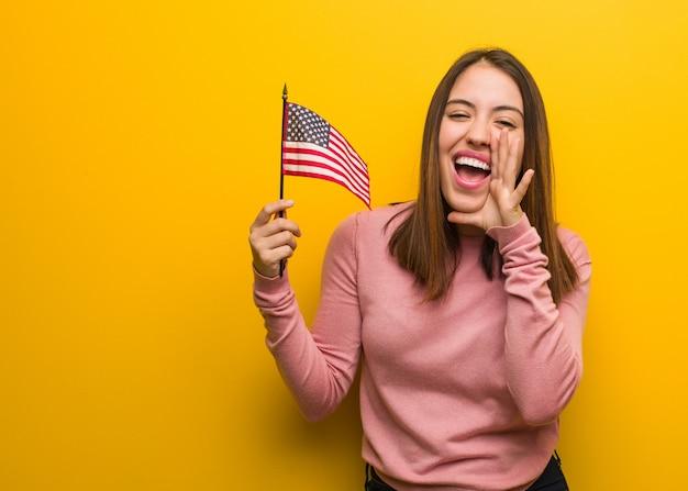 De jonge leuke vrouw die de vlag houdt van een verenigde staten schreeuwt iets gelukkig aan de voorzijde