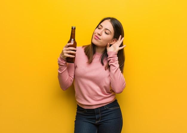 De jonge leuke vrouw die een bier houdt probeert aan het luisteren van een roddel