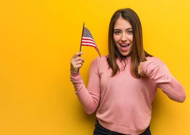 De jonge leuke vrouw die een verenigde staten houden markeert verrast, voelt succesvol en bloeiend