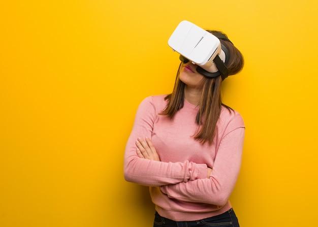 De jonge leuke vrouw die een virtuele werkelijkheid dragen googles glimlachend zeker en kruisend wapens, omhoog kijkend