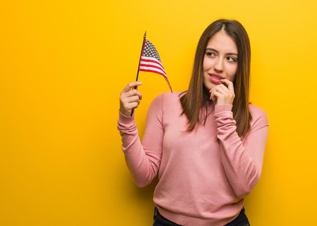De jonge leuke vrouw die een vlag houdt van de verenigde staten ontspande het denken over iets bekijkend een exemplaarruimte