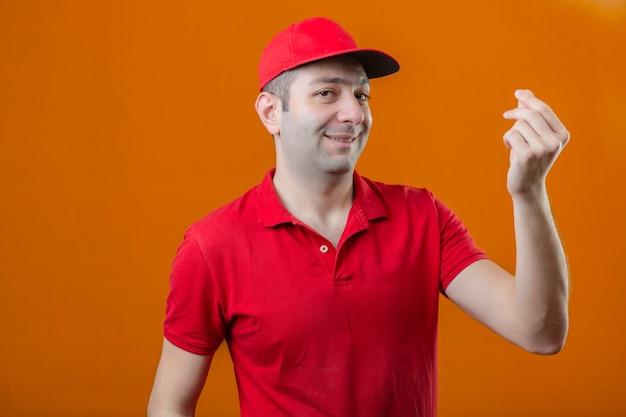 De jonge leveringsmens in rood poloshirt en glb met glimlach op gezicht die geldgebaar maken met overhandigt geïsoleerde oranje muur