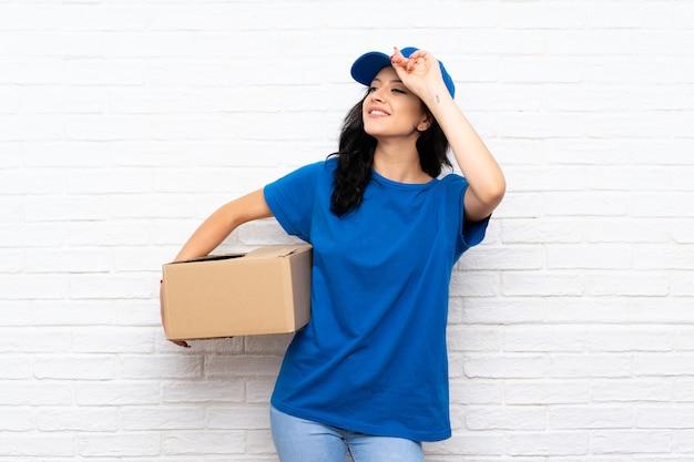 De jonge leveringsvrouw over witte bakstenen muur heeft iets gerealiseerd en de oplossing voorgenomen