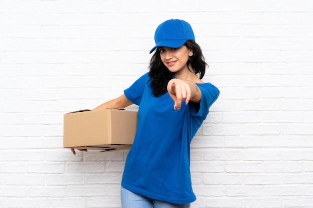 De jonge leveringsvrouw over witte bakstenen muur richt vinger op u met een zekere uitdrukking