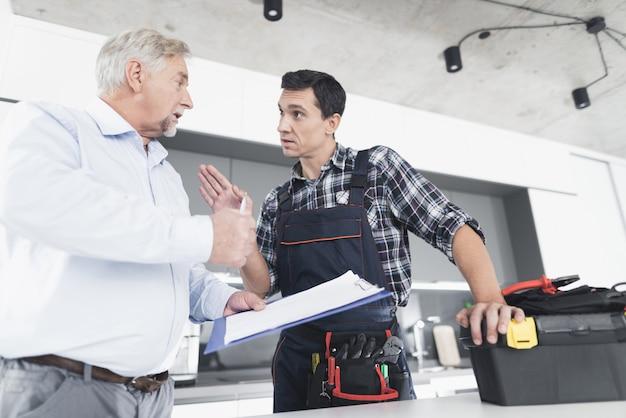 De jonge loodgieter communiceert met een oude man